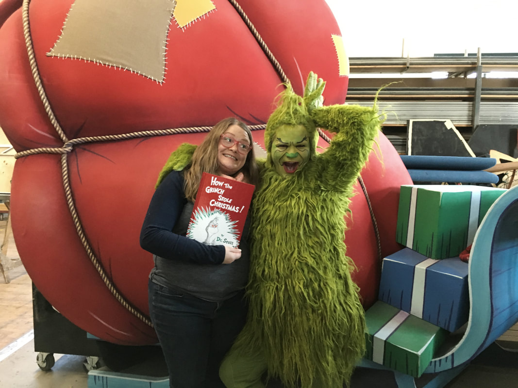 Pictured: Kendra and the Grinch pose in the CTC scene shop and a set piece that looks like a sleigh filled with a big Santa bag.